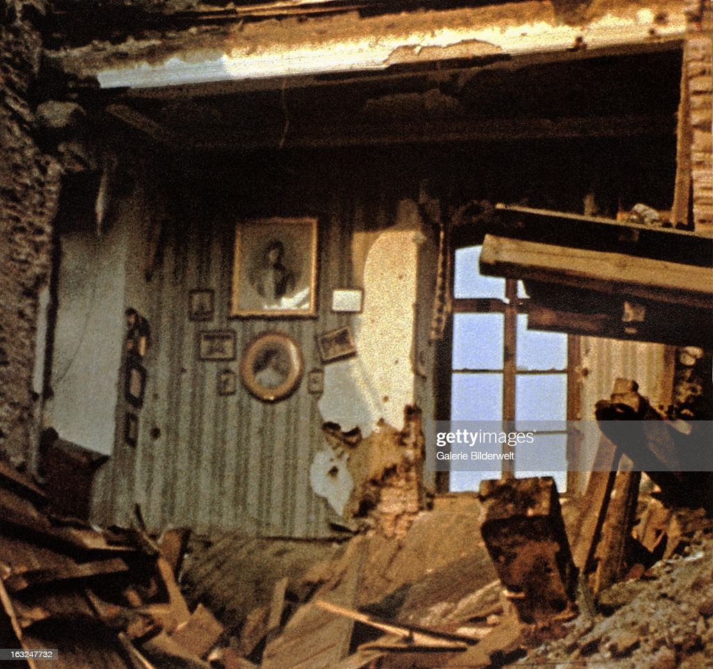 A house has been damaged by an aerial bomb which has destroyed the roof as well as the floor below. July 1945. Framed photos are still hanging on a wall. World War II, Germany.