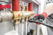 House Heating Valves and Pipelines Installing by Professional Caucasian Worker.