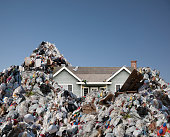 House in landfill surrounded by refuse