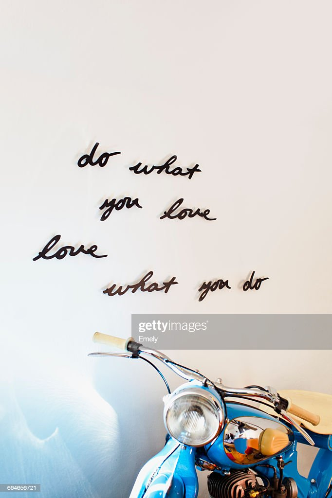 House interior wall with hand written positive motto design and motorcycle