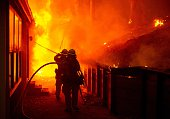 A house is engulfed in flames as firefighters attempt to put it out during the Valley fire in Seigler Springs California on September 13 2015 The...