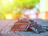 House keys with house figure on desk, out of focus background