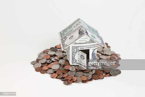 House made of paper money on top of pile of coins