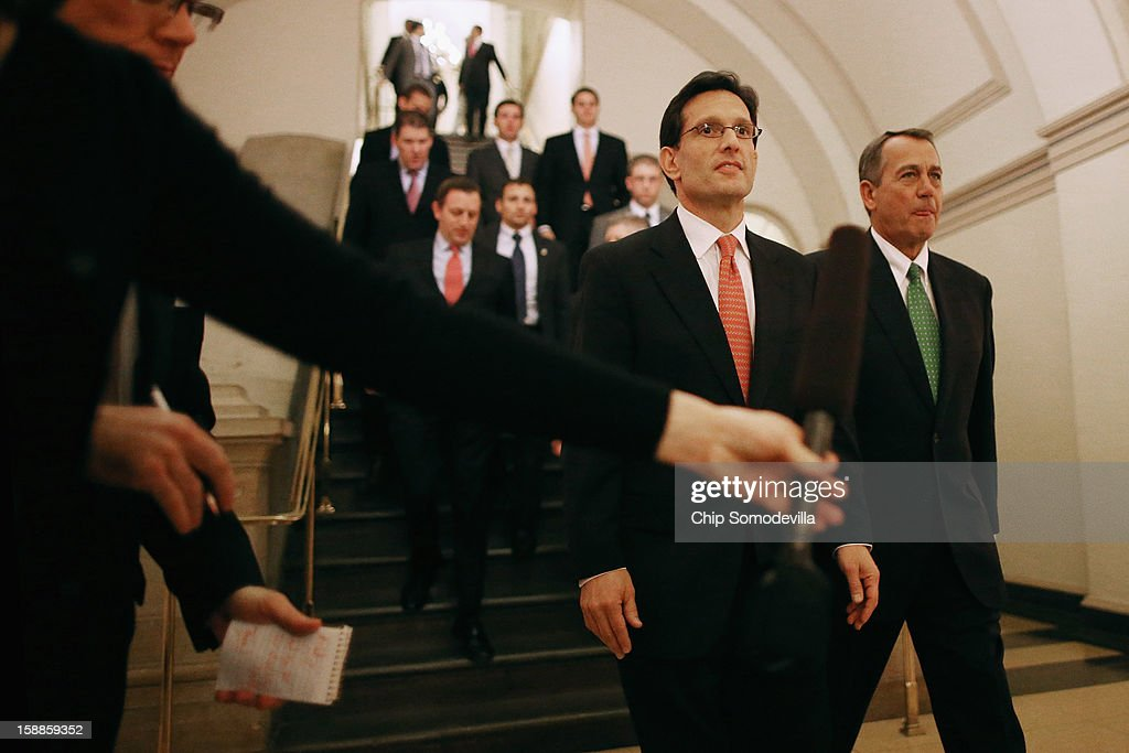House Majority Leader <a gi-track='captionPersonalityLinkClicked' href=/galleries/search?phrase=Eric+Cantor&family=editorial&specificpeople=653711 ng-click='$event.stopPropagation()'>Eric Cantor</a> (R-VA) (C) and Speaker of the House <a gi-track='captionPersonalityLinkClicked' href=/galleries/search?phrase=John+Boehner&family=editorial&specificpeople=274752 ng-click='$event.stopPropagation()'>John Boehner</a> (R-OH) (R) walk together to a meeting of the House Republican Caucus to discuss the Senate's legislation that is supposed to blunt the effects of the 'fiscal cliff' during a rare New Year's Day session January 1, 2013 in Washington, DC. Vice President Joe Biden and Senate Minority Leader Mitch McConnell (R-KY) negotiated the deal that produced The American Taxpayer Relief Act of 2012, which passed the Senate after midnight on New Year's Day.