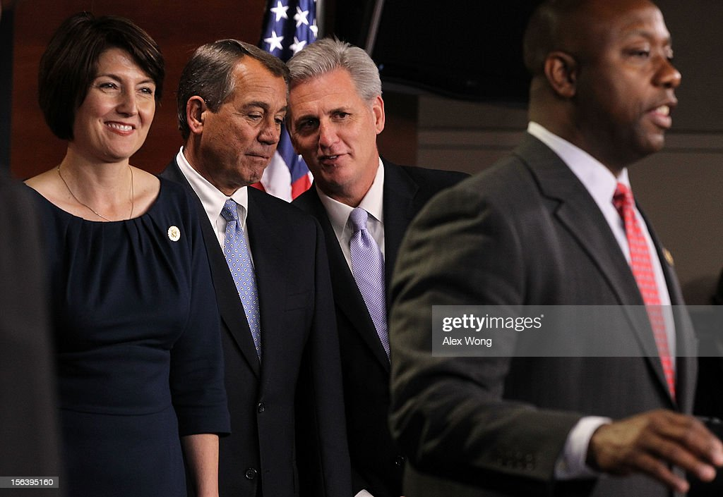 U.S. House Majority Whip Rep. Kevin McCarthy (R-CA) (3rd L) whispers to Speaker of the House Rep. <a gi-track='captionPersonalityLinkClicked' href=/galleries/search?phrase=John+Boehner&family=editorial&specificpeople=274752 ng-click='$event.stopPropagation()'>John Boehner</a> (R-OH) (2nd L) as Rep. Cathy McMorris Rodgers (R-WA) (L) smiles during a news conference to introduce the House Republican leadership for the next Congress November 14, 2012 on Capitol Hill in Washington, DC. The House Republicans have picked their choices of leadership for the 113th Congress.