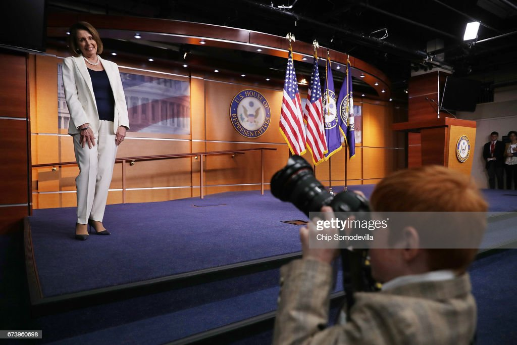 House Minority Leader Nancy Pelosi (D-CA) pauses while Archer Somodevilla, 7, takes a photograph during her weekly news conference at the U.S. Capitol Visitors Center April 27, 2017 in Washington, DC. Thursday was national Take Our Daughters and Sons to Work Day and many journalists brought their children to the U.S. Capitol. Pelosi gave President Donald Trump a letter grade for his performance as he approaches his 100th day in office.