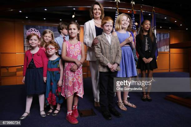 House Minority Leader Nancy Pelosi poses for photographs with journalists' children at the conclusion of her weekly news conference at the US Capitol...