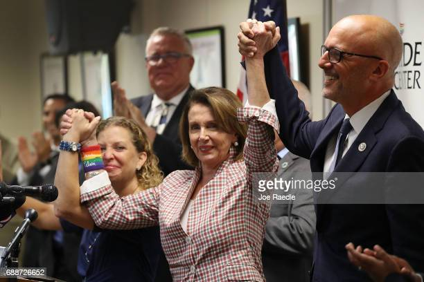 House Minority Leader Rep Nancy Pelosi Rep Debbie Wasserman Schultz and Rep Ted Deutch raise their arms together as they attend a discussion about...