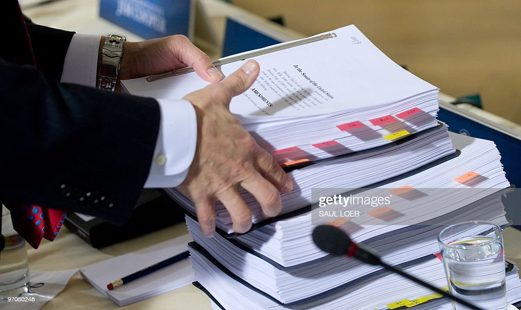 House Minority Whip Eric Cantor picks up a copy of the US Senate's healthcare reform plan HR 3590 prior to the start of a bipartisan meeting hosted...