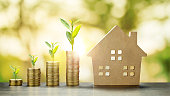 House Model and Golden Coins Stacks with blur Background.Savings Plans for Housing,Finance and Banking about House concept.