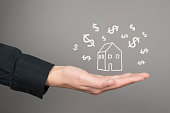 house model on human hands with dollar icon