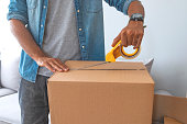Close up of male hand packing cardboard box, concept moving house. House moving concept. Happy young couple moving into new apartment with packaging boxes. Male hands packing cardboard box with scotch