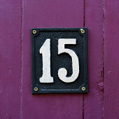 House number fifteen made out of cast metal.