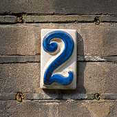 ceramic house number two on a brick wall.