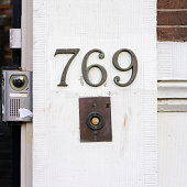 Bronze house number seven hundred and sixty nine above a doorbell, next to a door camera