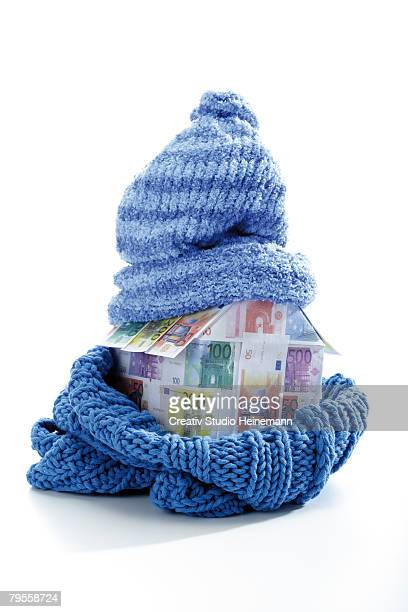 Model house of Euro notes wrapped in scarf and cap, close-up