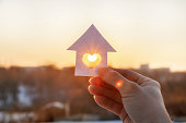 House of paper with a heart in the hand on the rising sun background.