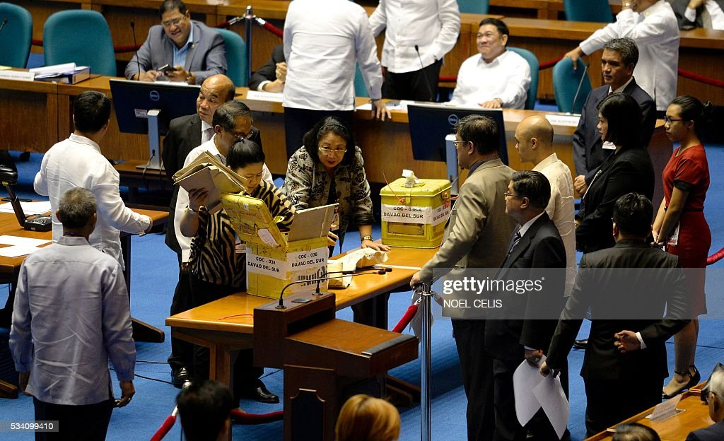 House of Representatives and Senate tribunal staff open a ballot box during the presidential and vice-presidential canvassing of votes at the session hall of House of Representatives in Manila on May 25, 2016. Incoming Philippine president Rodrigo Duterte has launched a series of obscenity-filled attacks on the Catholic Church, branding local bishops corrupt 'sons of whores' who are to be blamed for the nation's fast-growing population. / AFP / NOEL
