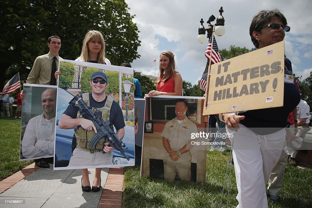 House of Representatives interns carry photographs of former Navy SEAL members Tyrone Woods and Glen Doherty and U.S. Foreign Service IT specialist Sean Smith during a Special Operations Speaks (SOS) Political Action Committee news conference demanding a House Select Committee investigate the Benghazi terrorist attck outside the U.S. Capitol July 23, 2013 in Washington, DC. SOS rolled out a 60-foot-long petition with the names of more than 1,000 Special Service veterans who support a full investigation of the September 11, 2012, Benghazi attacks.