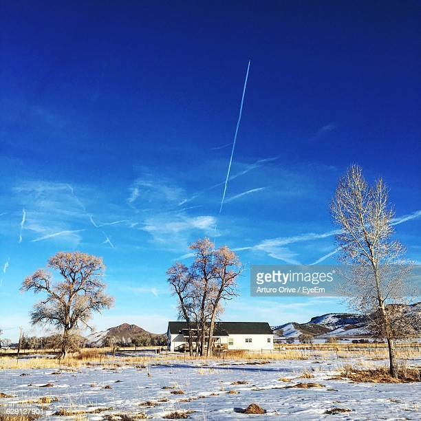 House On Field Against Vapor Trails In Sky