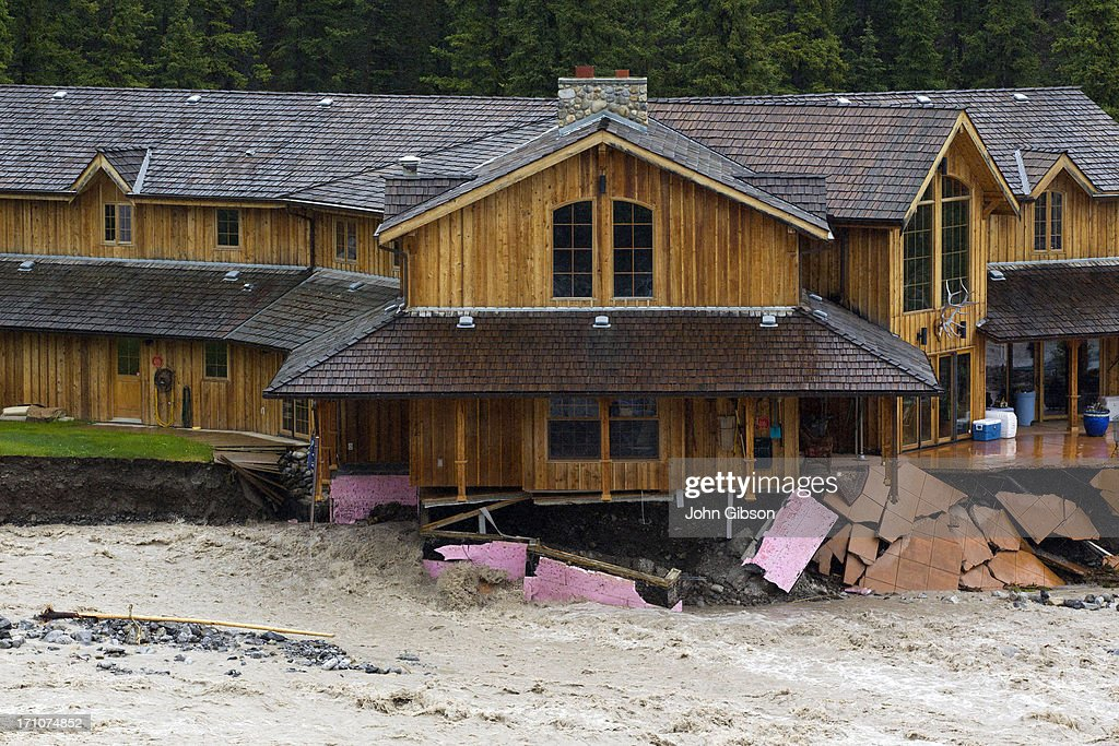 A house on the banks of Cougar Creek suffers damage during flooding on June 21 2013 in Canmore Alberta Canada Widespread flooding caused by...