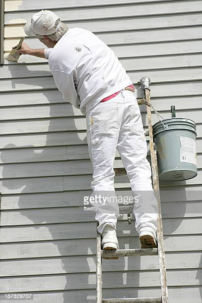 House painter leaning towards left to apply paint
