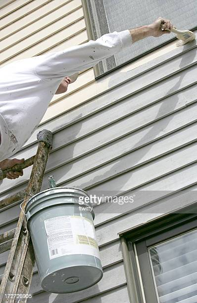 House painter on ladder, leaning to reach a corner