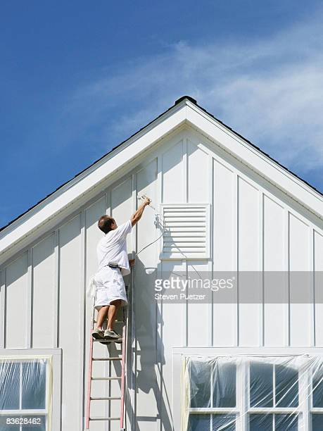 House painter on ladder painting exterior