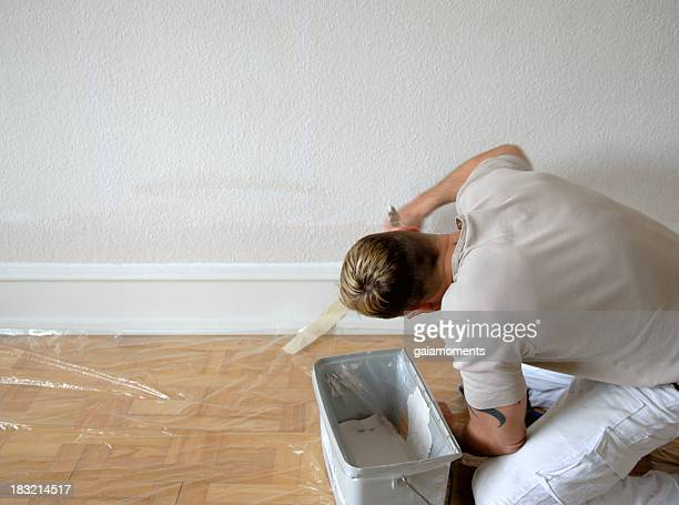 House painter painting a white skirting board in a room