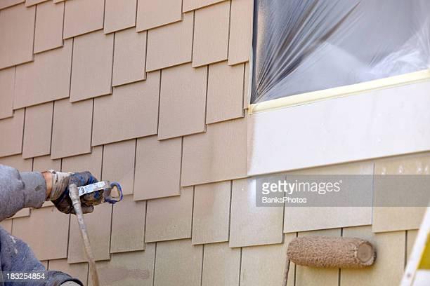 Peintre pulvérisation de peinture sur la nouvelle façade