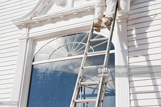 House painter standing on a ladder leaning on a house