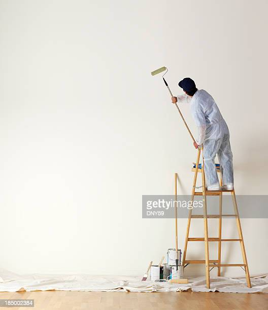 House painter standing on ladder una gran pared de pintura