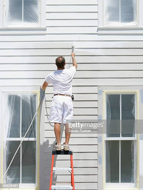 House painter standing on ladder painting exterior