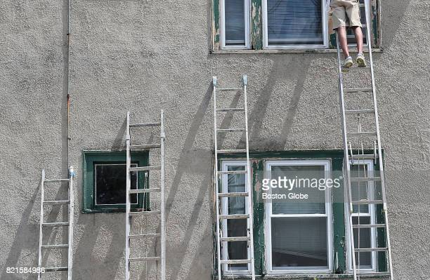 A house painter stands on a ladder outside a home on Charlesbank Road in Newton MA on Jul 10 2017