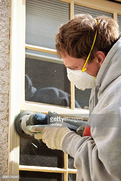 Peintre à l'aide d'un outil électrique Sander, préparation de la fenêtre pour des travaux de peinture