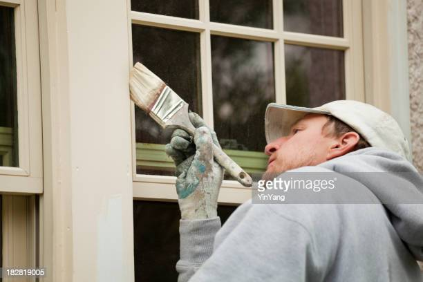 House Painter Working on Exterior Home Maintenance Improvement Painting Work