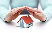 hands covering house - insurance concept - real estate
