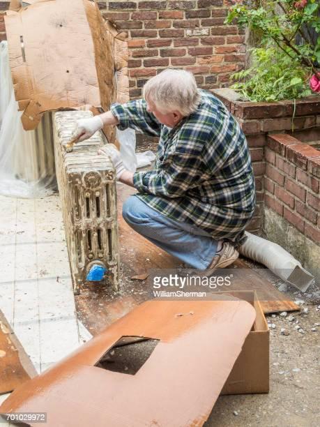 Haus Renovierung - Senior woman Chipping Farbe aus einem alten Heizkörper im Regen
