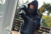 house robbery - burglar with face mask opens balcony doors with crowbar