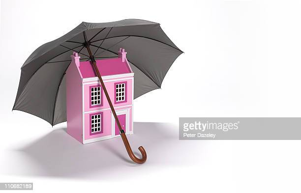 House sheltered by umbrella with copy space