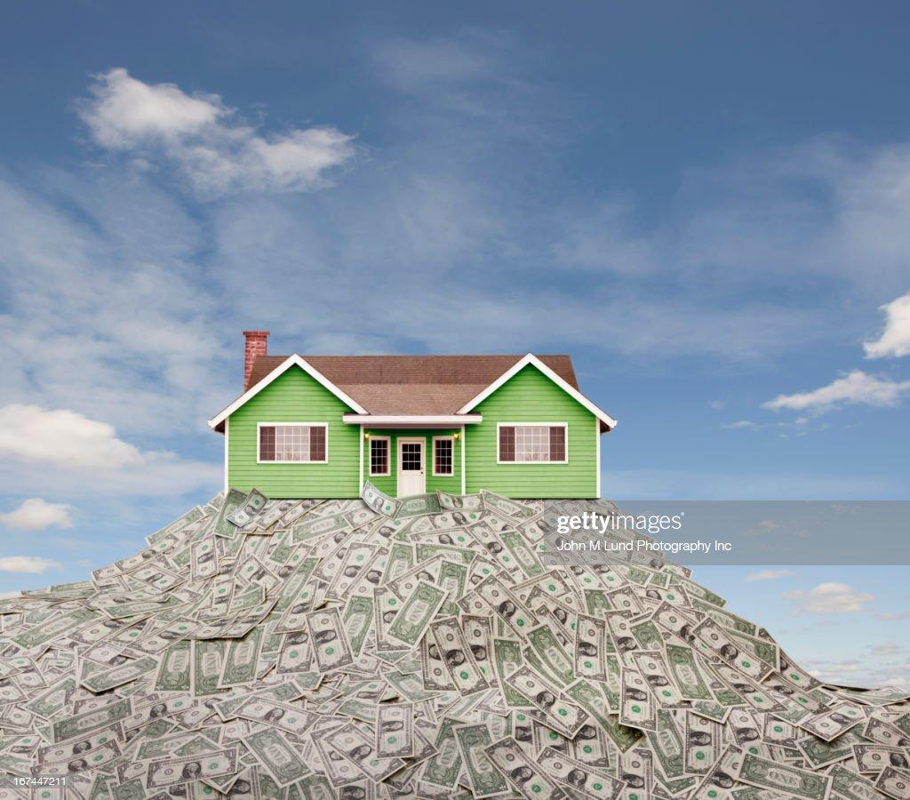 House sitting on pile of dollar bills