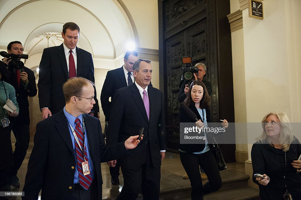 House Speaker John Boehner, a Republican from Ohio, center, leaves the U.S. Capitol, surrounded by members of the media, on his way to a meeting with U.S. President Barack Obama in Washington, D.C., U.S., on Friday, Dec. 28, 2012. President Obama is set to propose a scaled-back package at a meeting with congressional leaders to avert tax and spending changes that could trigger a recession in 2013, a Democratic aide with knowledge of the talks said. Photographer: Jay Mallin/Bloomberg via Getty Images