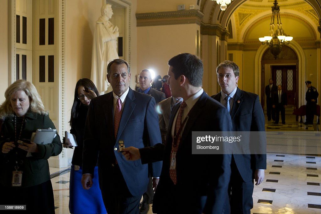 House Speaker John Boehner, a Republican from Ohio, center left, is surrounded by members of the media as he walks through the U.S. Capitol in Washington, D.C., U.S., on Sunday, Dec. 30, 2012. Senate Majority Leader Harry Reid rejected the latest Republican offer to resolve the U.S. fiscal crisis as Minority Leader Mitch McConnell reached out to Vice President Joe Biden in an effort to break the impasse. Photographer: Andrew Harrer/Bloomberg via Getty Images