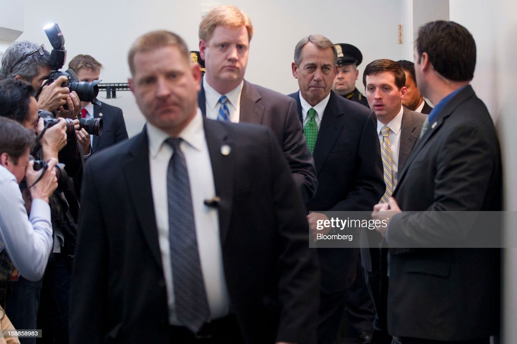 House Speaker John Boehner, a Republican from Ohio, center rght, walks out of a House Republican caucus meeting at the U.S. Capitol in Washington, D.C., U.S., on Tuesday, Jan. 1, 2013. The U.S. Senate passed a bipartisan budget deal two hours after income tax cuts expired, reaching an after-deadline agreement to undo the potential economic harm of $600 billion in tax increases and spending cuts. Photographer: Andrew Harrer/Bloomberg via Getty Images