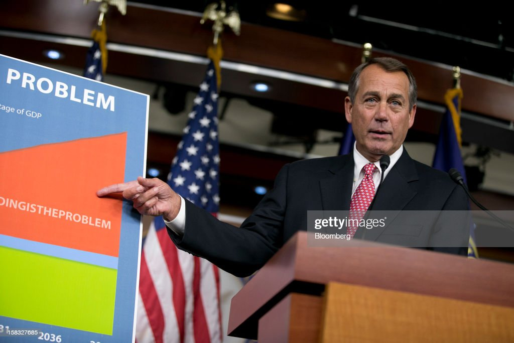 House Speaker <a gi-track='captionPersonalityLinkClicked' href=/galleries/search?phrase=John+Boehner&family=editorial&specificpeople=274752 ng-click='$event.stopPropagation()'>John Boehner</a>, a Republican from Ohio, points to a sign during a news conference in Washington, D.C., U.S., on Thursday, Dec. 13, 2012. Boehner repeated his insistence that President Barack Obama's budget proposal is 'anything but' balanced and accused the president of being 'not serious' about cutting spending. Photographer: Andrew Harrer/Bloomberg via Getty Images
