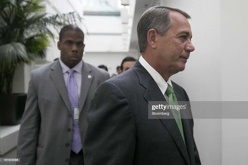 House Speaker John Boehner, a Republican from Ohio, right, leaves a news conference following a meeting in Washington, D.C., U.S., on Thursday, Sept. 26, 2013. Boehner's choice -- between keeping the government running and continuing to fight the nation's three-year-old health-care law - has implications for the 2014 congressional elections and, potentially, his future. Photographer: Andrew Harrer/Bloomberg via Getty Images