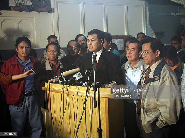 House Speaker Manuel Villar center stands with opposition congressmen from the lower house of Congress November 3 2000 as they announce their...