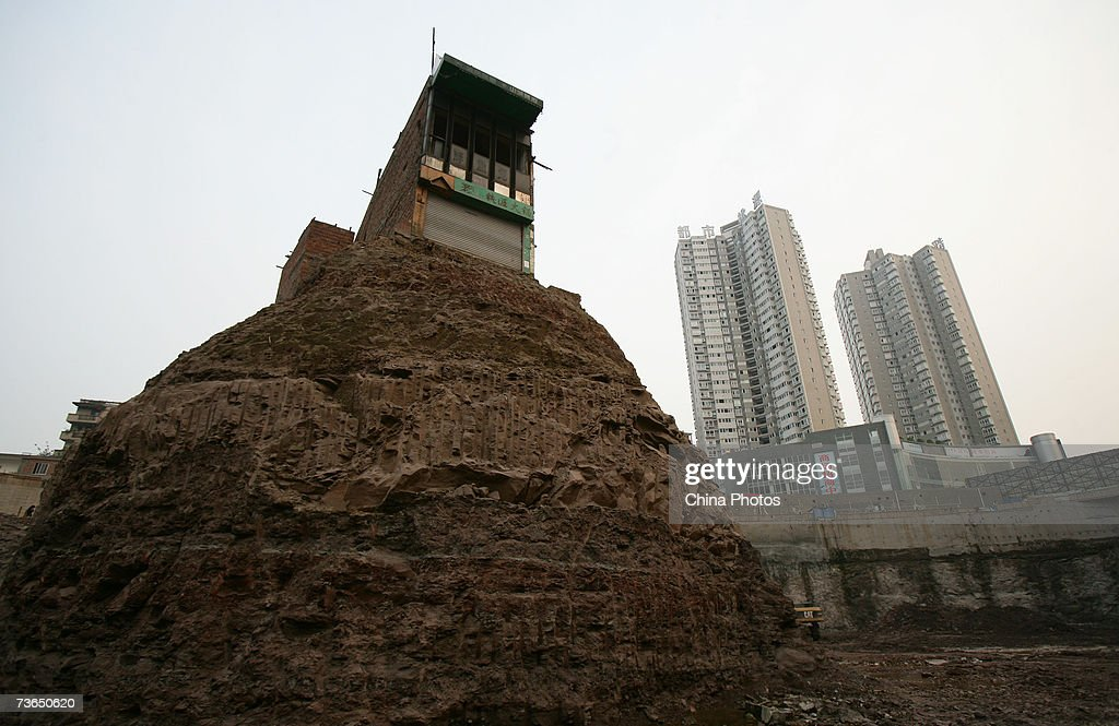 A house whose owner refused to accept a compensation deal by a property developer is surrounded by the ongoing excavation at a construction site on...