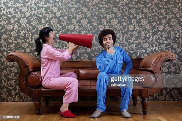 House Wife Shouting At Husband Via Megaphone On Sofa