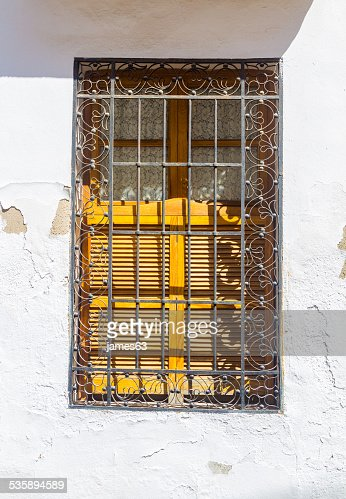 house window decorated with iron bars : Stock Photo